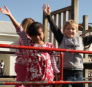 2 children on the playground with arms in the air.
