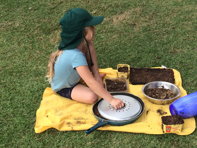 Student making mud pies outside.