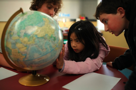 Students and teacher looking at a globe.