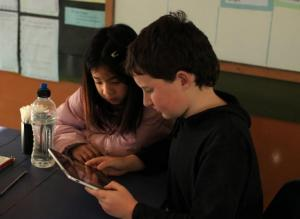 Students looking at an iPad.