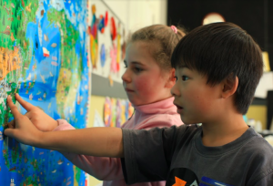 Students pointing to a world map.